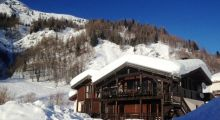 Chalet in sun with snow